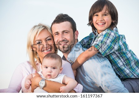 Young parents with a smiling son and a baby posing