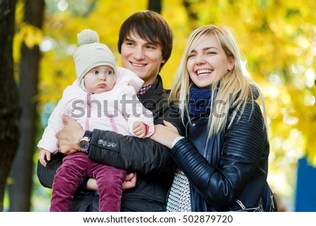 Young parents with baby in autumn park among trees