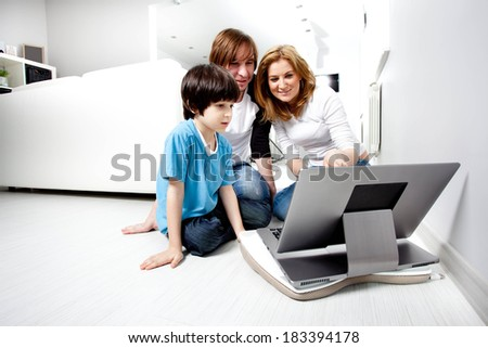 Young parents with child near laptop computer - stock photo