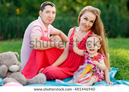 Young parents with daughter and book sitting on plaid