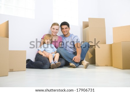 Young parents with daughter sitting on the floor between cardboard boxes. They're looking at camera. Low angle view.
