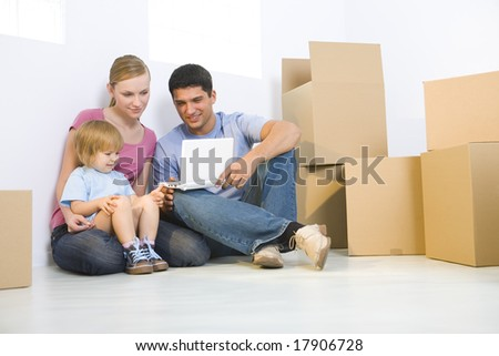Young parents with daughter sitting on the floor between cardboard boxes. They're looking at laptop. Low angle view.