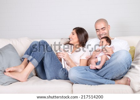 Young parents with little baby at home, sitting on cozy divan, enjoying family, loving couple with newborn daughter, positivity and fun concept  - stock photo