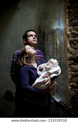 Young parents with little baby boy in the old house - stock photo