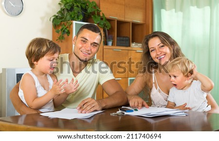 Young parents with little children buying insurance and smiling - stock photo