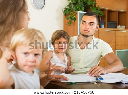 Young parents with little children having conflict in home interior  - stock photo