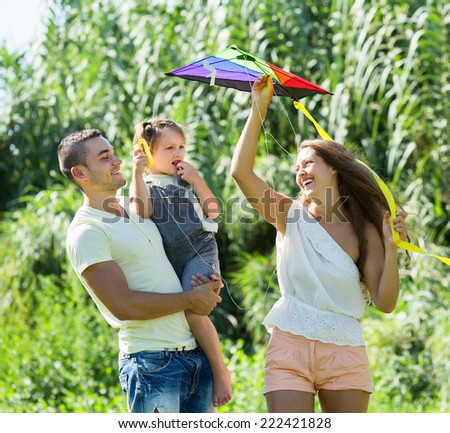 Young parents with little daughter and colorful kite on vacation day
