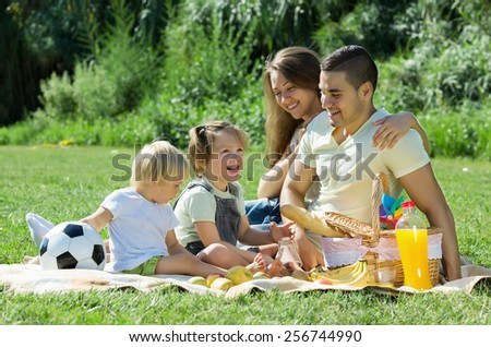 Young parents with little daughters having holiday with picnicin in summer