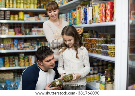 Young parents with little girl buying tinned food at grocery  - stock photo