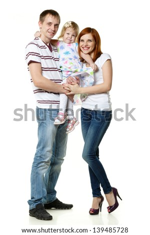 Young parents with lovely daughter stand on a white background. Happy family. - stock photo