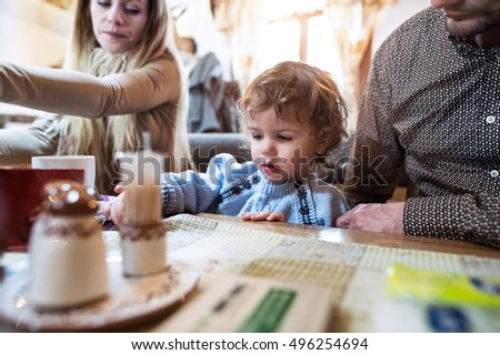 Young parents with son in restaurant waiting for meal.