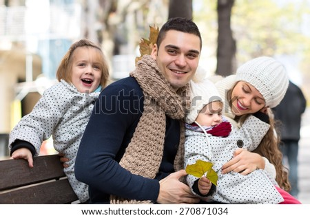 Young parents with their children sitting outside on a bench and having fun. Shallow focus. Focused on a man. - stock photo