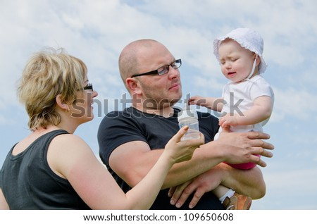 Young parents with their one year old daughter - stock photo