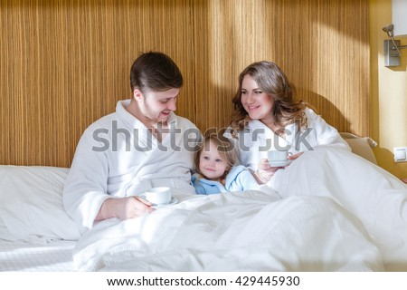 Young parents with their sweet daughter lies on a bed in a bedroom in the morning. Happy family. - stock photo