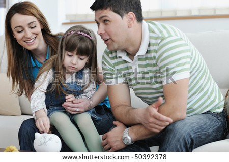 young parrent at home with beautiful child make savings and put coins money in piggy bank