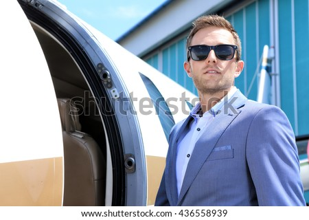 Young passenger wearing sunglasses by the entry door of the Executive jet