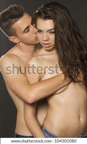 Young passion couple topless on gray isolated background