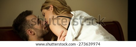 Young passionate couple during foreplay in bed - stock photo