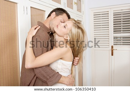 Young passionate couple kissing in home's bedroom. - stock photo