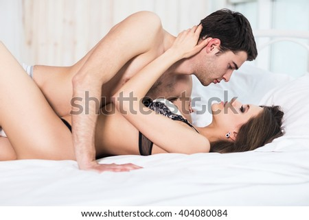 Young passionate couple lying in bed