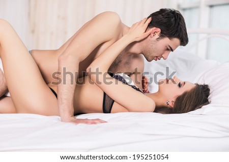 Young passionate couple making love in bed - stock photo