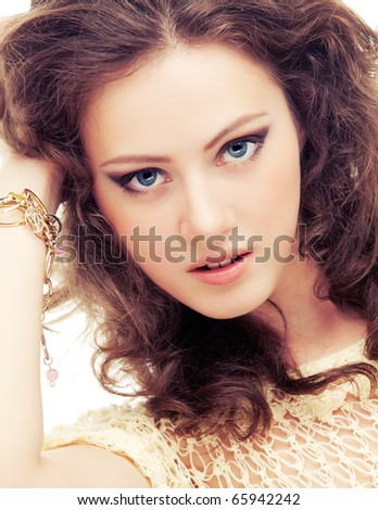 Young passionate woman in bracelets of gold, isolated on white background.