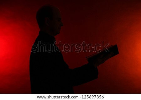 Young pastor with Bible, on dark red background