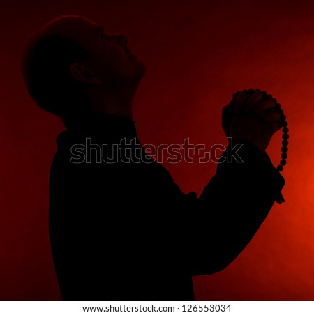 Young pastor with wooden rosary, on dark red background - stock photo