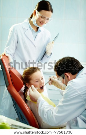 Young patient undergoing usual check-up procedure at dentist�¢??s - stock photo
