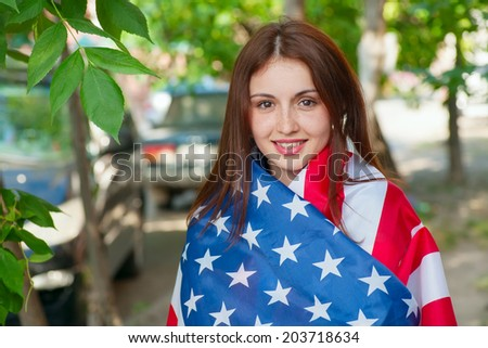Young patriotic girl warped in US flag smiling outdoors.