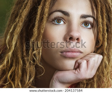 Young pensive beautiful woman with dreadlocks in red clothes closeup. - stock photo