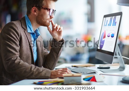 Young pensive businessman in eyeglasses working in office - stock photo