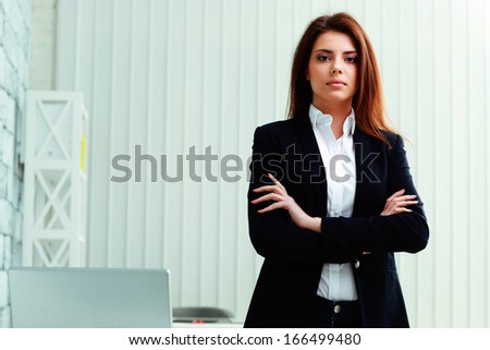 Young pensive businesswoman standing with arms folded at office