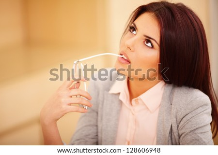 Young pensive casual businesswoman with glasses looking up - stock photo