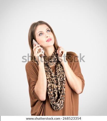 Young pensive or bored woman while talking on the cellphone over gray background with vignette. - stock photo