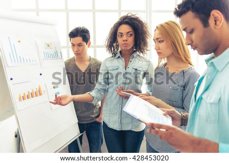 Young pensive people of different nationalities are discussing business affairs while examining graphs - stock photo