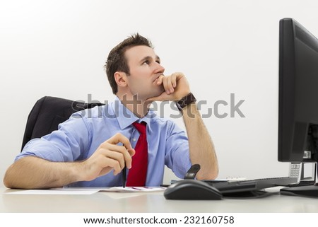 Young pensive undecided businessman in blue shirt and red tie looking up while leaning his chin on his hand. Searching for business solutions. - stock photo