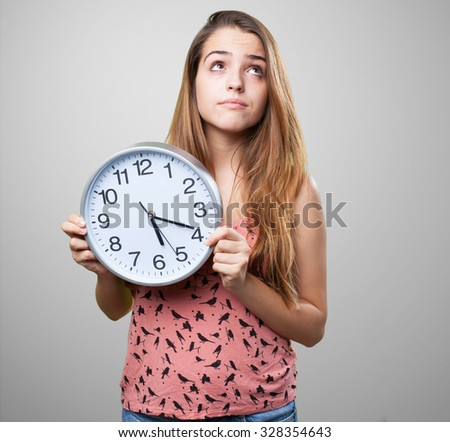 young pensive woman holding a clock on white