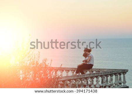 Young pensive woman holding and embracing male child boy sitting on stony parapet looking on sunset outdoor near sea water on natural background, horizontal picture - stock photo