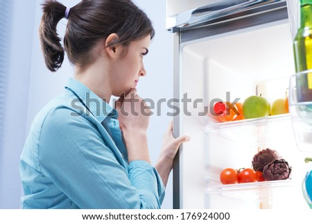 Young pensive woman looking in the refrigerator with hand on chin. - stock photo