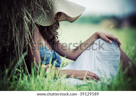 Young pensive woman resting on a field. - stock photo