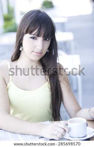 Young pensive woman with coffee - stock photo
