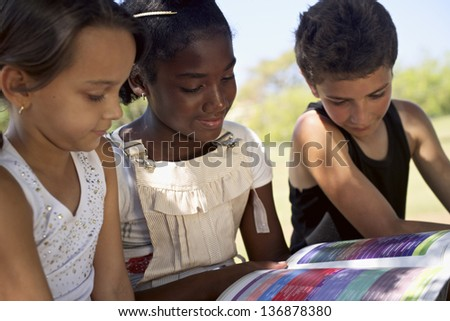 Young people and education, two little girls and one boy reading book in city park