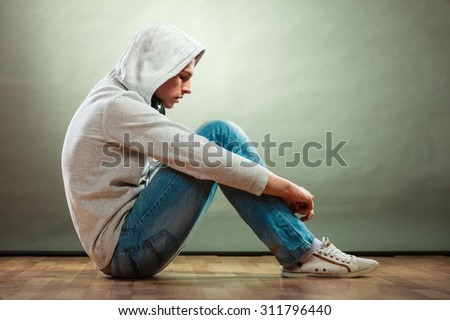 Young people and emotions concept. Sad hooded man teen boy with headphones sitting on floor grunge background - stock photo