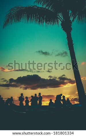 Young People At Retro Styled Hawaiian Sunset Beach Party - stock photo