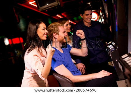 Young people at slot machine in the casino - stock photo