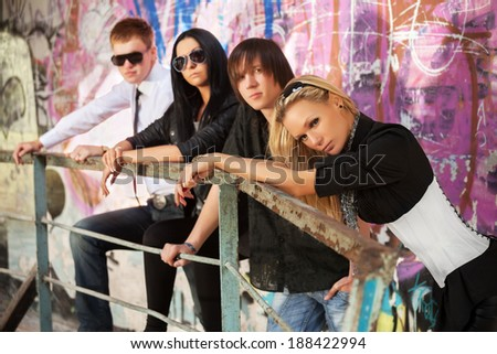 Young people at the graffiti wall - stock photo