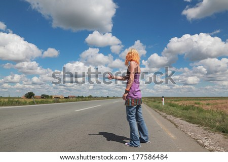 Young people, Caucasian girl hitch hiking at a road