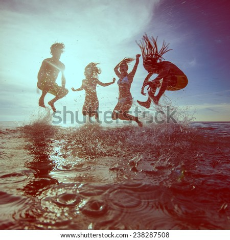 young people dancing and spraying at the beach - stock photo