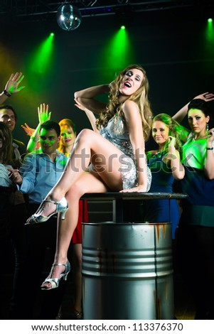 Young people dancing in club or disco and have party, the girls and boys, friends, having fun - stock photo